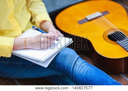Closeup songwriter having fun enjoy hobby concept and writing on note paper with acoustic guitar near by. Learning musical instrument.
