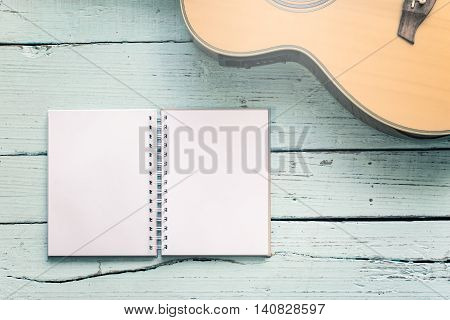 The diary blanks with an acoustic guitar on the wooden table of music composer for musical notes.