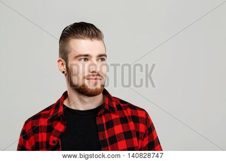Young handsome man posing, smiling over grey background. Copy space.