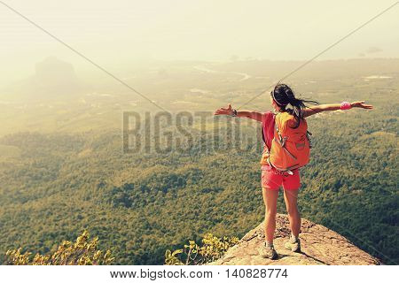 young asian woman hiker enjoy the view on mountain peak cliff