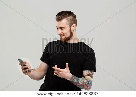 Young handsome man looking at phone, smiling over grey background.  Copy space.