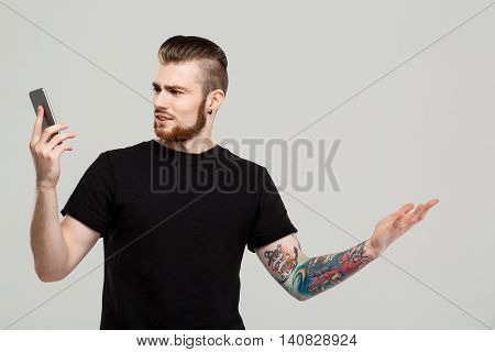 Young handsome man looking at phone, disappointed over grey background.  Copy space.