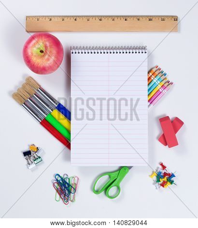 Top view of back to school concept with traditional supplies on white background.