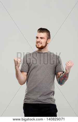 Young handsome man rejoicing, shouting over grey background. Copy space.