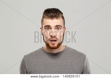 Surprised young handsome man posing, looking at camera over grey background. Copy space.