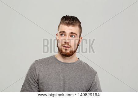 Young handsome man posing, looking in side over grey background. Copy space.