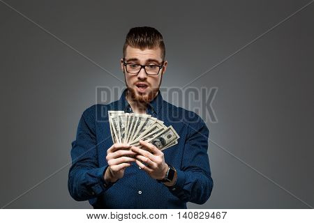Young successful businessman in glasses surprised, holding money over dark background. Copy space.