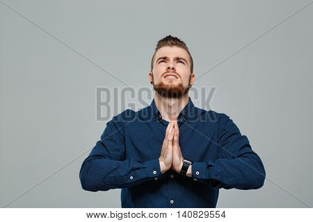 Young successful businessman praying, looking above over grey background. Copy space.