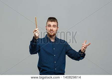Young successful confident businessman posing over grey background. Copy space.