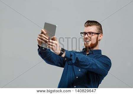Young successful businessman in glasses looking at tablet, smiling over grey background. Copy space.