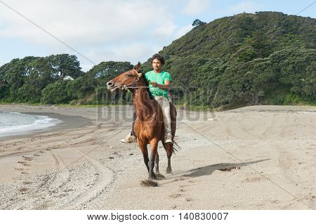 Young Maori man in green tee shirt rides along Ta Kaha beach on brown horse