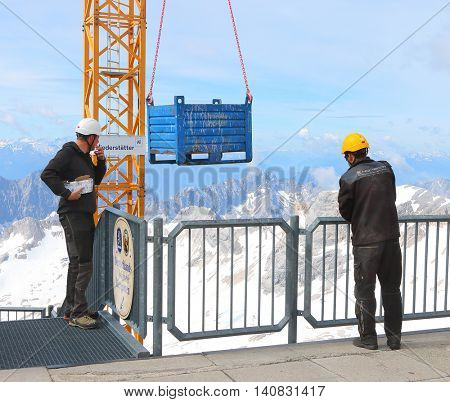 ZUGSPITZE GERMANY - JULY 5, 2016: Unidentified workers and Liebherr crane 150 EC-B on Germany's highest construction site in 2962m. Building the new Zugspitze cable car for tourists and skiers.