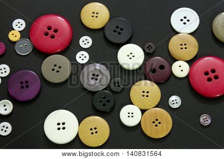 This is a photograph of colorful sewing buttons on a black background