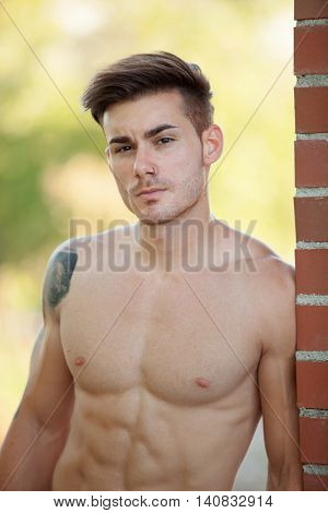 Handsome fit athletic shirtless young man with a tattoo leaning against a brick wall