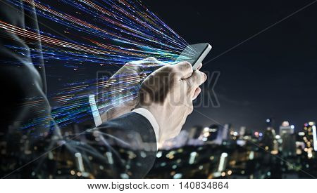 Businessman using mobile phone with defocus nightlife city background