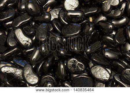 This is a photograph of Black Glass nuggets