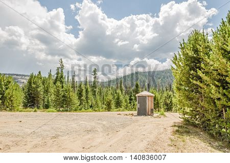 Beautiful clouds against a blue sky bright green trees surrounding a wide area for an isolated round outhouse and smoky mountains due to two forest fires in the area.