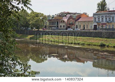 UZHGOROD UKRAINE - AUGUST 3 2015: River Uzh in Uzhhorod near the pedestrian bridge connecting the city with the oldest part of Uzhgorod. There are many tourists always