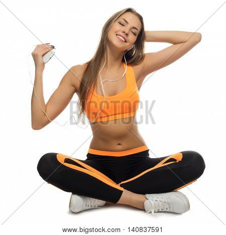 Young sporty girl listen music isolated