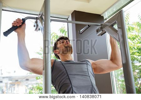 Attractive young sportsman doing exercises and training in gym
