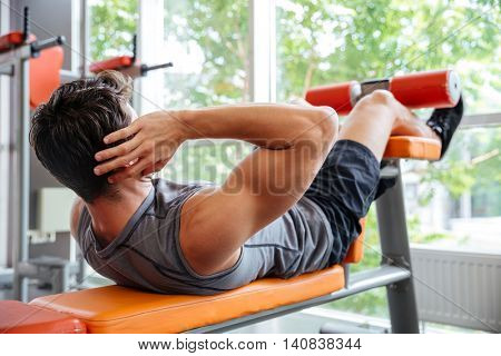 Young sports man doing bench press workout at the gym