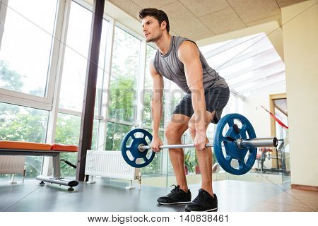 Concentrated young sportsman standing and lifting barbell in gym