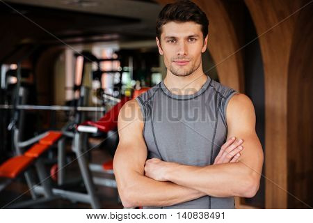 Attractive young sportsman standing with arms crossed in gym