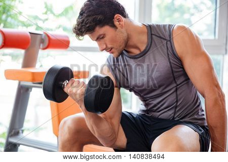Concentrated young fitness man working out with dumbbells in gym