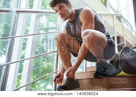 Handsome young man athlete sitting and tying laces on stairs