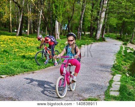 Bikes bicyclist girl. Two sister girls wearing bicycle helmet and glasses with rucksack rides bicycle. Bicyclist children is looking camera. Children sisters ride on green grass and flowers in park.