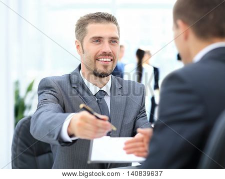 Businessman giving a pen to seal a deal with his partner