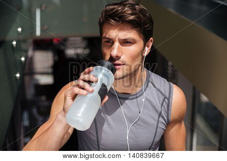 Handsome young sportsman drinking water and listening to music