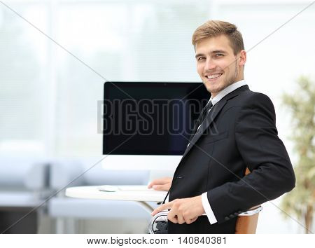 Image of businessman working in office in front of his laptop co