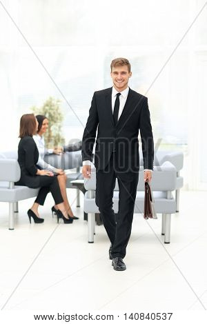 Handsome business man standing with his collegues in background