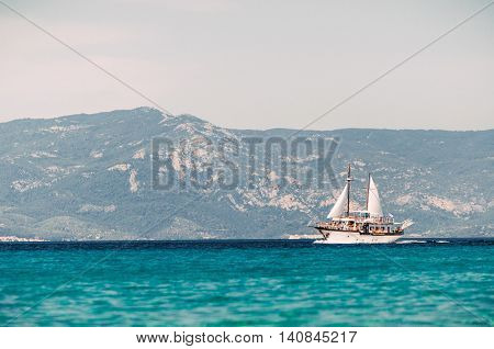 PEFKOHORI GREECE - MAY 26 2015: Sailing ship sails in the Aegean Sea on the background of mountains and hills of the peninsula Sithonia Halkidiki.