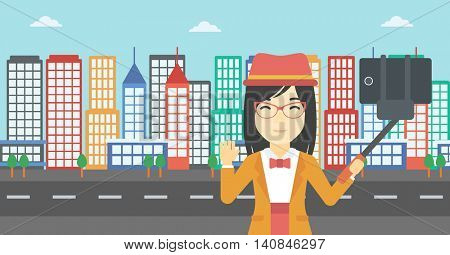 An asian woman making selfie with a selfie-stick. An asian woman taking photo with cellphone and waving on a city background. Vector flat design illustration. Horizontal layout.