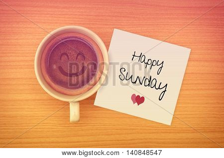 Happy Sunday on paper note with coffee cup,top view.