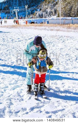 Bansko, Bulgaria - December 12, 2015: The small child learning to ski with mother in Bansko, Bulgaria