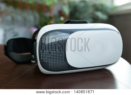 virtual reality glasses on wooden table blurred background.
