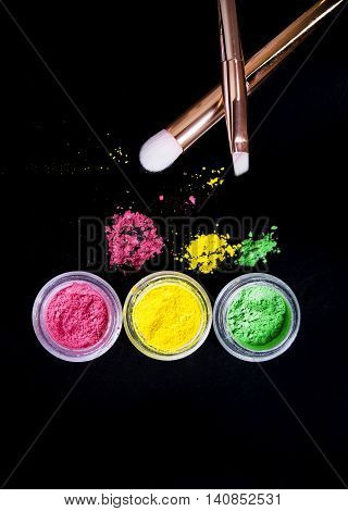 Set of colorful mineral eye shadows with brushes on black background