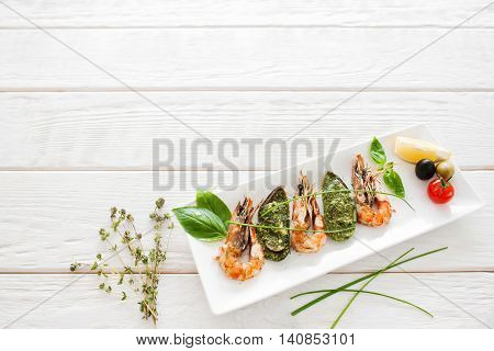 Delicious seafood mix on white wooden background, copyspace. Tasty mediterranean meal with shrimps and mussels, free space for text, restaurant serving