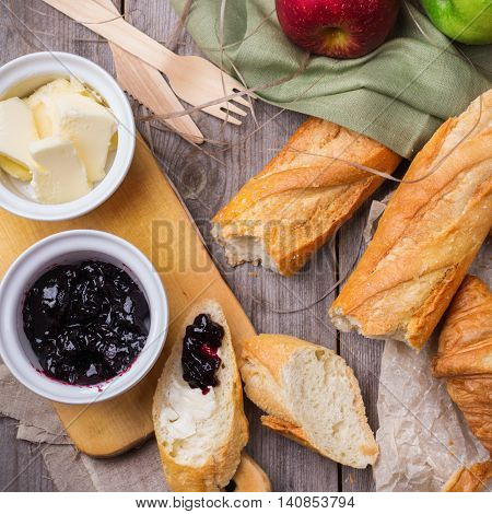 Still life, food and drink concept. French baguette with butter and jam and croissant for breakfast on a rustic wooden table. Selective focus, top view