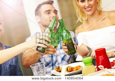 Picture presenting group of friends with beer during bbq party