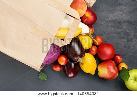 Paper bag with different of vegetables and fruits on dark surface top view