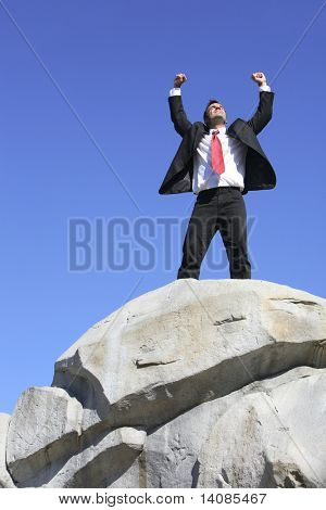 Businessman on top of rock with arms outstretched