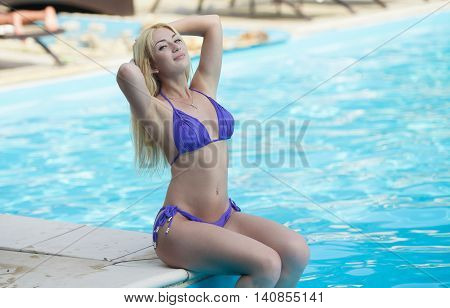 young attractive blonde woman in purple bikini in pool.