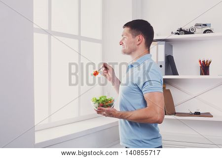 Man has healthy business lunch in modern office interior. Young handsome businessman profile portrait looking at window with vegetable salad in bowl, diet and eating right concept. High key image
