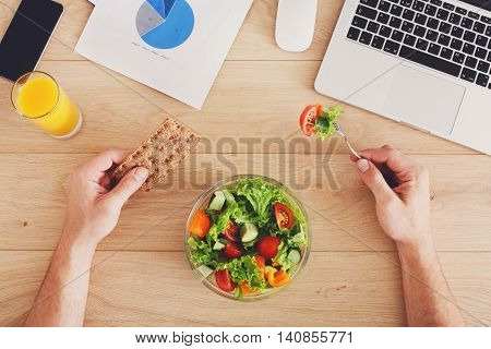 Business lunch at working place. Businessman in office. Hands of eating man. Healthy, diet food, vegetable salad with apple and juice. Cell phone, laptop and papers. Top view, flat lay