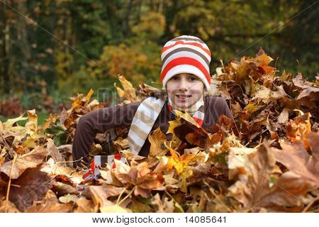 Young girl sitting in pile of leaves