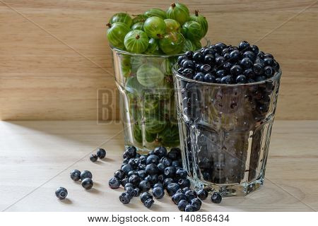 Blueberries and gooseberries in a glass with scattered berries. Good addition for breakfast